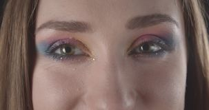 Closeup shoot of young pretty caucasian short haired female face with glitter makeup looking at camera with background stock video footage