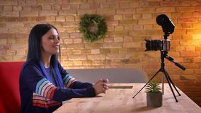 Closeup shoot of young pretty female video blogger streaming live talking on camera and waving hello smiling indoors in stock video