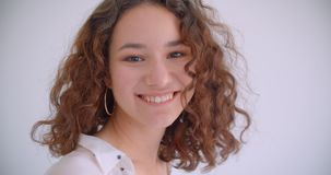 Closeup shoot of young pretty long haired curly caucasian female smiling happily turning and looking at camera with. Background isolated on white stock video footage