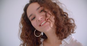 Closeup shoot of young pretty long haired curly caucasian female smiling happily turning and posing in front of the. Camera with background isolated on white stock video