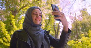 Closeup shoot of young pretty muslim female in hijab having a video call on the phone smiling happily in the park. Outdoors stock video
