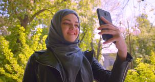 Closeup shoot of young pretty muslim female in hijab taking selfies on the phone smiling happily in the urban city. Outdoors stock footage