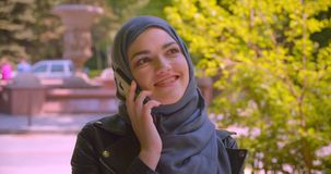 Closeup shoot of young pretty muslim female in hijab talking on the phone smiling happily on the street in the urban. City outdoors stock footage