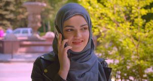 Closeup shoot of young pretty muslim female in hijab talking on the phone smiling happily in the urban city outdoors.  stock video
