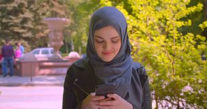 Closeup shoot of young pretty muslim female in hijab using the phone looking at camera smiling happily in the urban city. Outdoors stock video