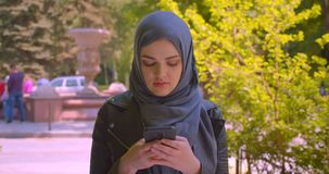 Closeup shoot of young pretty muslim female in hijab using the phone smiling happily in the urban city outdoors.  stock video footage