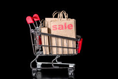 Closeup shopping cart with sale paper bags is isolated on black Stock Photography