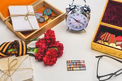 Closeup shot of alarm clock, eyeglasses, flowers wrapped by st. george ribbon, letters, medals on gray, victory day concept royalty free stock photo