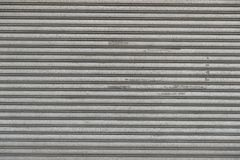 A closeup shot of automatic metal roller door used in factory, storage, garage, and industrial warehouse. The corrugated and foldable metal sheet offer space stock photo