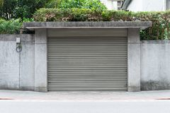 A closeup shot of automatic metal roller door used in factory, storage, garage, and industrial warehouse. The corrugated and foldable metal sheet offer space stock image