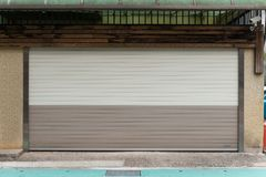 A closeup shot of automatic metal roller door used in factory, storage, garage, and industrial warehouse. The corrugated and foldable metal sheet offer space royalty free stock photo