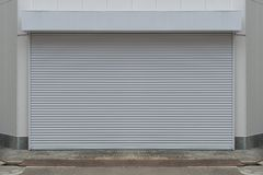 A closeup shot of automatic metal roller door used in factory. Storage, garage, and industrial warehouse. The corrugated and foldable metal sheet offer space stock photography