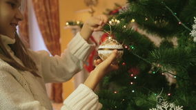 Closeup shot of beautiful girl hanging golden bauble on Christmas tree stock video