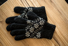 Closeup shot of black knitted gloves lying on wooden table stock images