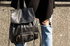 Closeup shot of  black leather backpack at the woman`s legs. Closeup photo of  black leather backpack at the woman`s legs Royalty Free Stock Images