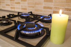 Closeup shot of blue fire from domestic kitchen stove. Gas cooke. R with burning flames propane gas and candle. Old and new concept royalty free stock images