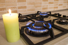 Closeup shot of blue fire from domestic kitchen stove. Gas cooke. R with burning flames propane gas and candle. Old and new concept royalty free stock image