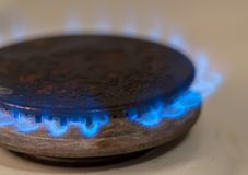 Closeup shot of blue fire from domestic kitchen stove. Gas cooker with burning flames propane gas.  stock image