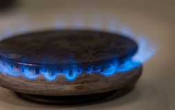 Closeup shot of blue fire from domestic kitchen stove. Gas cooker with burning flames propane gas.  stock photo