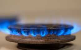 Closeup shot of blue fire from domestic kitchen stove. Gas cooker with burning flames propane gas.  stock photos