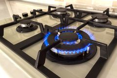 Closeup shot of blue fire from domestic kitchen stove top. Gas c. Ooker with burning flames of propane gas. Industrial resources and economy concept stock images