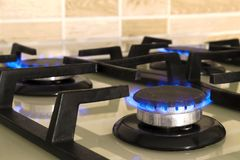 Closeup shot of blue fire from domestic kitchen stove top. Gas c. Ooker with burning flames of propane gas. Industrial resources and economy concept stock photography