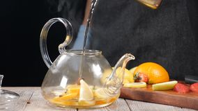 Closeup shot of boiled water being poured into teapot wuth fruit. Tea brewing concept. Slow motion. Pouring water in stock video footage