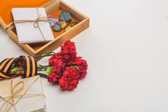 closeup shot of box with medals, stacks of letters, carnations wrapped by st. george ribbon on gray, victory day concept stock images