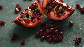 Ripe pomegranate halves on board. Closeup shot of bright shiny seeds and halves of juicy pomegranate on rough table stock photos