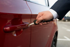 Closeup shot of businessman opening parked car with key Royalty Free Stock Photos