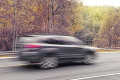 SUV car in motion during fall season royalty free stock photography
