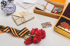 Closeup shot of carnations wrapped by st. george ribbon, letters, medals in boxes and alarm clock, victory day concept stock photography