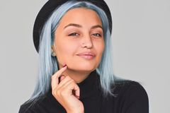 Closeup shot of cheerful and charming teenager woman with blue hair wearing black apparel and hat, smiling. Cute positive female. Posing on light grey royalty free stock photo