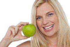 Closeup shot of a cheerful woman holding an apple Royalty Free Stock Photos