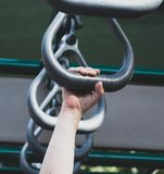Young child`s hand gripping playground equipment. Closeup shot of a child`s right hand climbing on playground metal rights Stock Photos