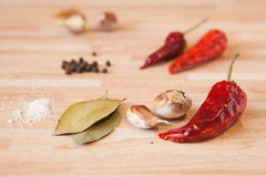 Closeup shot of chili pepper. Bay leaf, garlic, salt with spices on background on light wooden table. Cuisine background Stock Image