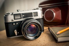Closeup shot of classic film camera and notebook on wooden desk Stock Image