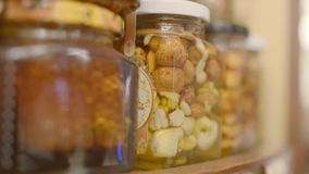 Honey with nuts. Closeup shot of colorful honey with fruit and nuts in the jar, on a market. Cashew and hazel nut stock footage