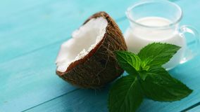Cup of milk and half of coconut. Closeup shot of composed glass of milk and coconut half with mint leaves on blue-colored wooden table stock footage