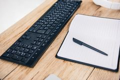 Closeup shot of computer keyboard, empty textbook with pen and headphones. At table royalty free stock image