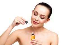 Closeup shot of cosmetic oil applying on young woman`s face stock photo