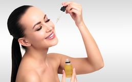 Closeup shot of cosmetic oil applying on young woman`s face stock image