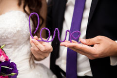 Closeup shot of couple. Holding violet love word Royalty Free Stock Photos