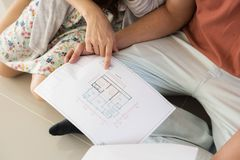 Couple read paper blueprint for interior plan. Closeup shot of couple read paper blueprint to design interior plan of decoration at wall and ceiling. First Royalty Free Stock Images