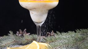 Closeup shot of delicious dessert in glass bowl on wooden board decorated with fir-tree branches and slices of lemon. Isolated on black background. Pouring stock video