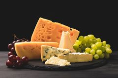 Closeup shot of different types of cheese on board with grapes on black stock image