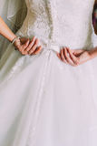 Closeup shot of elegant, bride in vintage white dress fixing her dressing at wedding preparations. Back view Stock Images