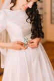 Closeup shot of elegant, brunette bride in vintage white dress fixing her dressing before wedding Royalty Free Stock Image