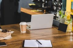 Closeup shot of empty textbook, paper cup of coffee and laptop. In coffee shop royalty free stock photos