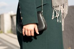 Closeup shot of fashionable dressed woman in green coat wearing. Little black purse. Closeup shot Royalty Free Stock Photography